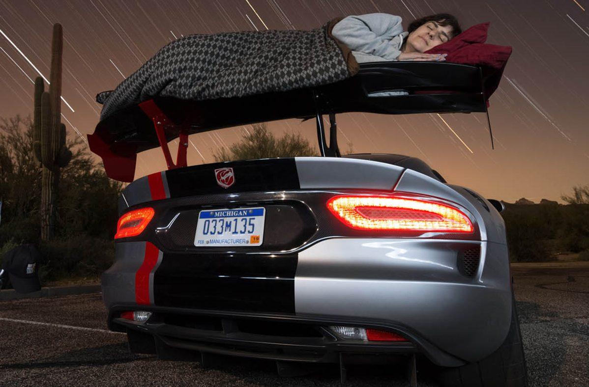 Pessoa a dormir na asa traseira do Dodge Viper