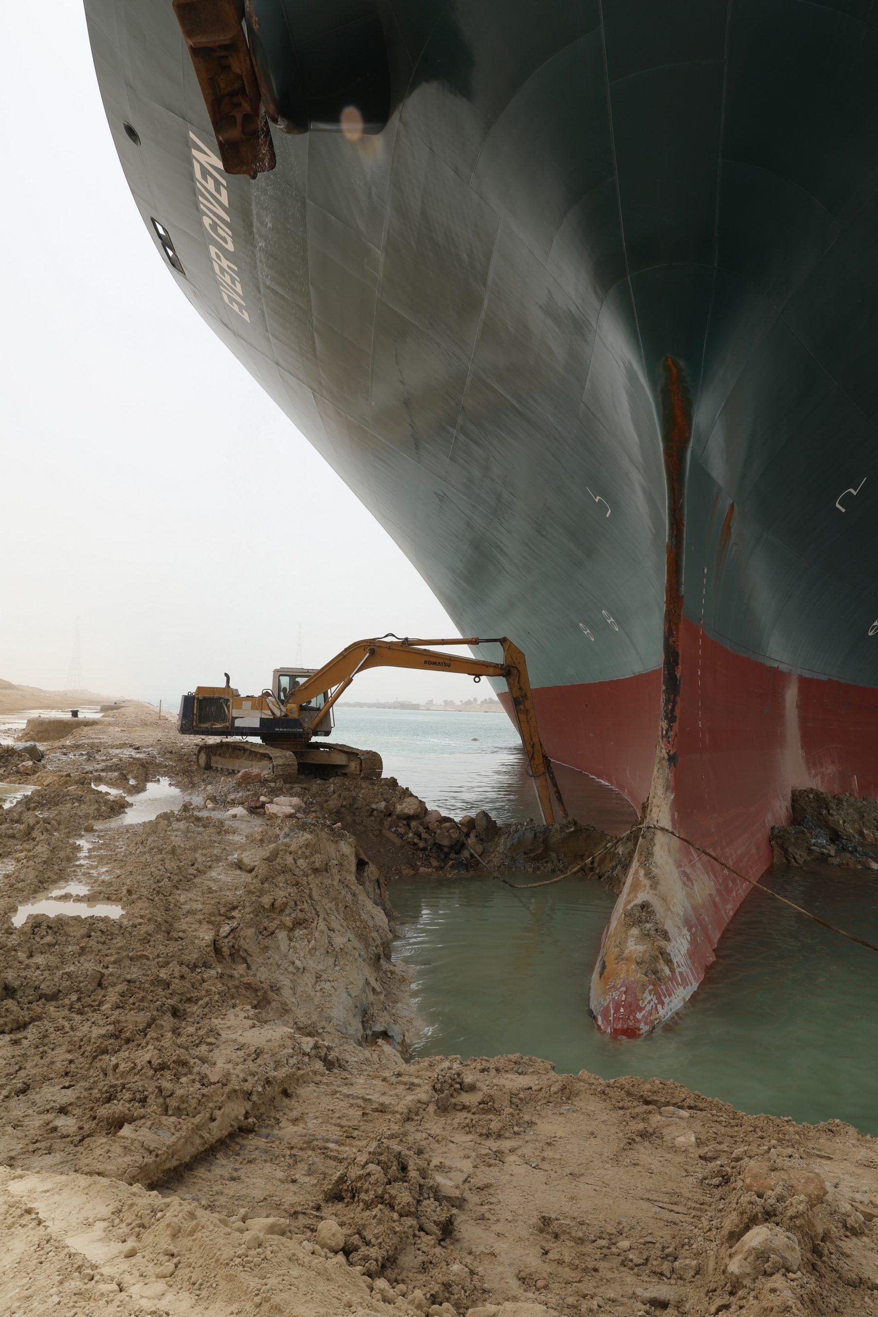 Escavadora a retirar areia para desancalhar Ever Given
